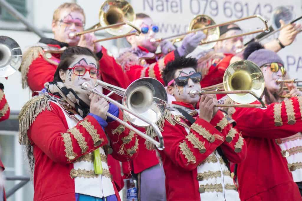 Trombonists in band uniforms playing music.