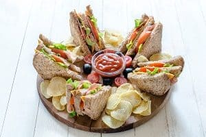 Tray of sandwiches, chips, and dip for family celebrations.