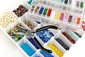 Pliers on plastic boxes full of multicolored beads