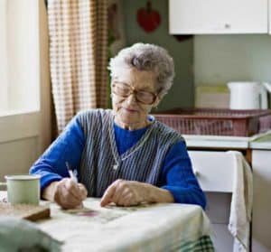 Country grandmother writes down the things she wants to learn next.
