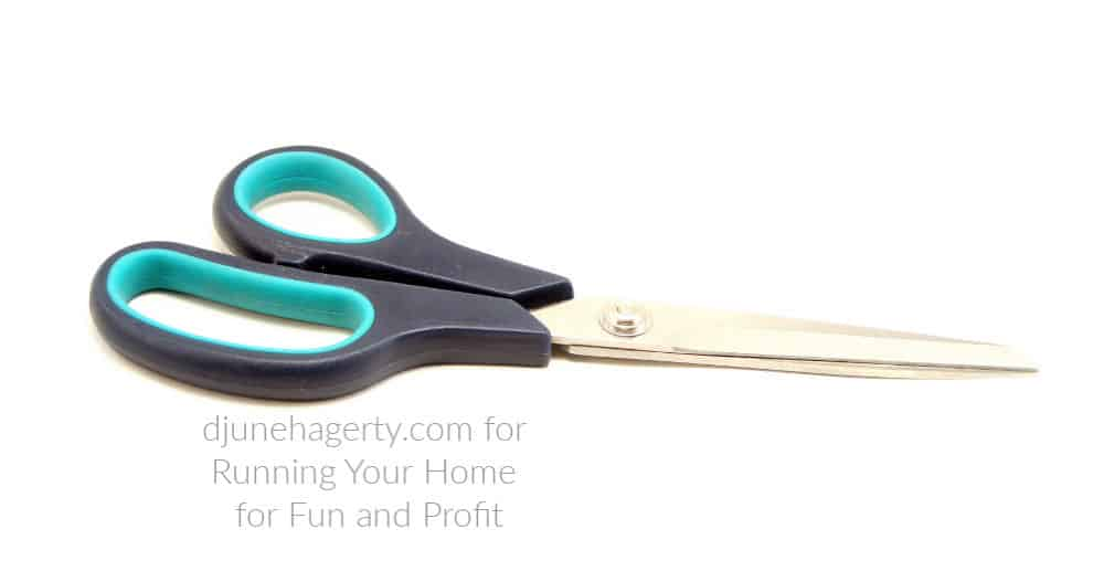 Scissors with black and aqua handles to used for sewing.