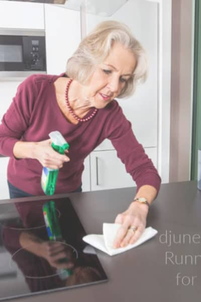 Older woman using spray bottle and cleaning cloth to clean kitchen counter.