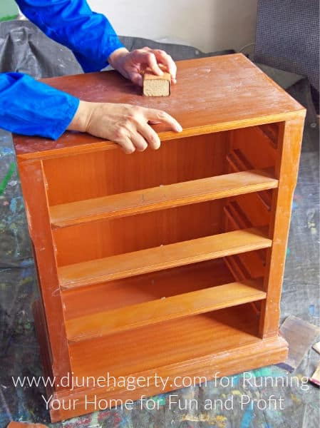 A man's hand clean a wood bookcase