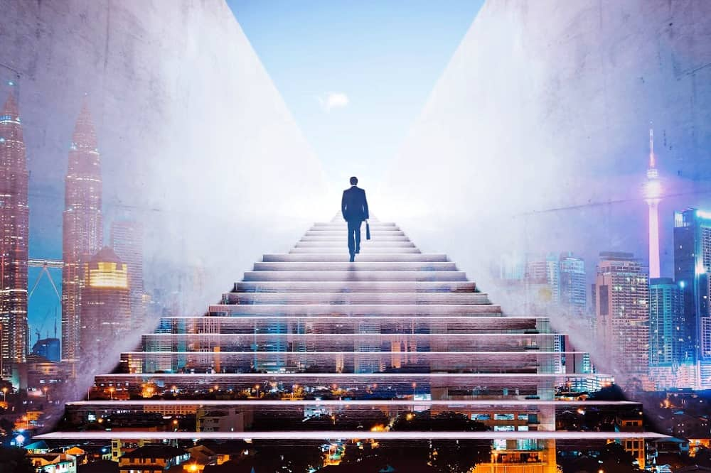 A man in suit with briefcase climbing stairs into sky, superimposed over a cityscape.